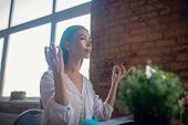 Beautiful Calm Young Woman Meditating At Work poster