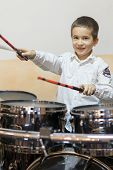 Boy Drumming. Boy In A White Shirt Plays The Drums. A Boy In A White Shirt Is Drumming. Vertical Pho poster