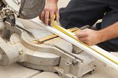 image of baseboard  - Contractor Measuring for Circular Saw Cutting of New Baseboard Renovation - JPG