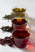 Three Glass Cups With Black, Red And Green Tea On A White Background. Red Hot Hibiscus Tea With Dry  poster