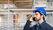 Portrait of a worker talking on the phone in a contruction site poster
