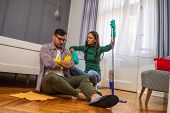 Man Is Lazy. His Wife Is Telling Him To Continue Cleaning Their Apartment. poster