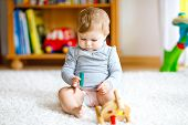 Adorable Baby Girl Playing With Educational Toys . Happy Healthy Child Having Fun With Colorful Diff poster