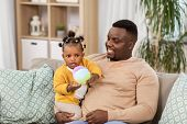 family, fatherhood and people concept - happy african american father with baby daughter at home poster
