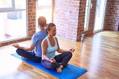 Middle age beautiful sporty couple sitting on mat practicing yoga doing lotus pose at gym poster