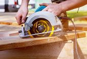 Builder Saws A Board With A Circular Saw In The Cutting A Wooden Plank poster