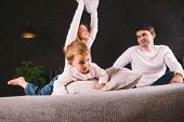 Parents With Smiling Child Playing Pillow Fight On Bed, Happy Family Having Fun In Bedroom, Enjoying poster