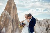 Couple In Love Hugs And Kisses In Fabulous Mountains In Nature. Girl In Long White Dress With Bouque poster