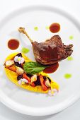 Fried duck leg with young vegetables, flowers and carrot cream on white restaurant plate isolated. R poster