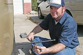 Mechanic using a tire iron to remove lug nuts from an automobile tire.