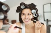 Woman In Curlers Applying Makeup