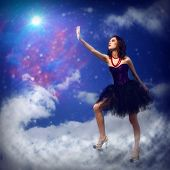picture of reach the stars  - Young woman reaching for a glowing star - JPG