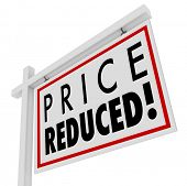 stock photo of negotiating  - Price Reduced words on a home for sale sign to illustrate a home owner in distress and needing to sell immediately as a short sale or negotiated lower value to the right buyer - JPG