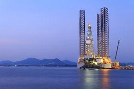 foto of shipyard  - Jack up oil drilling rig in the shipyard for maintenance at sunset time - JPG