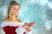 image of outfits  - Pretty girl holding hands out in santa outfit against blurred christmas background - JPG