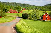stock photo of farm landscape  - old red farm houses set in a rural landscape and nature - JPG