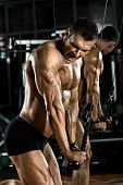 foto of execution  - very power athletic guy bodybuilder execute exercise with gym apparatus on triceps - JPG