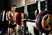 stock photo of execution  - very power athletic guy execute exercise with weight - JPG