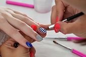 foto of finger-painting  - Finger nail treatment painting lines with brush and lacquer - JPG