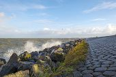 pic of dike  - Basalt stones along a dike in a stormy sea - JPG