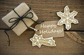 stock photo of ginger bread  - White Happy Holidays on a brown Banner with Ginger Bread Cookies and a Gift all on Wood - JPG