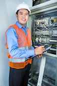 pic of breaker  - Asian Indonesian Technician or electrician making function test on breaker box or switch box with power lines on construction site or in factory for acceptance - JPG