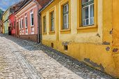 stock photo of cobblestone  - Idyllic cobblestone street with colourful buildings in Sighisoara - JPG