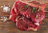 foto of porterhouse steak  - Beef Steak with Seasoning and fresh herbs on wooden board - JPG