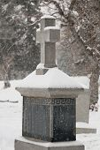 stock photo of tombstone  - snow covered tombstone with cross in cemetary - JPG