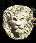 stock photo of garden sculpture  - Sculpture of lions head in garden courtyard - JPG