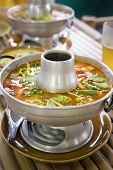 image of gai  - Tom yum soup in traditional dishware in a street restaurant - JPG