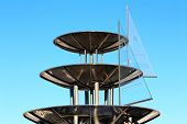 stock photo of metal sculpture  - Fountain consisting of three metallic bowls on the background of sky - JPG