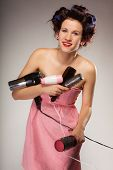 image of hair curlers  - Young woman preparing for date having fun cute girl with curlers styling hair with many accessories comb brush hairdreyer on gray - JPG