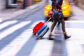 stock photo of zebra crossing  - Two women with suitcases crossing street on zebra crossing - JPG