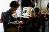 pic of sewing  - Middle aged woman sewing in a sewing workshop - JPG