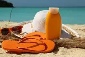 image of sun tan lotion  - Sun tan lotion on a sandy beach with a sun hat and glasses - JPG
