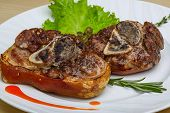 pic of roasted pork  - Roasted pork knee with thyme rosemary and salad leaves - JPG