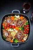 image of roasted pork  - Tasty roasted pork meat with mushrooms and vegetable  - JPG