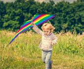 stock photo of kites  - little cute girl flying a kite in a meadow on a sunny day - JPG