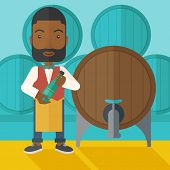 picture of inspection  - An african wine maker standing wearing his apron holding a bottle of wine inspecting from barrel inside the wine storage room - JPG