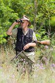 foto of shotgun  - Senior hunter with shotgun looking through binoculars in forest - JPG