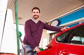 picture of petrol  - Man refuelling a car at a petrol station - JPG