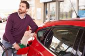 picture of petrol  - Young man refuelling a car at a petrol station - JPG