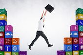 stock photo of leaping  - Businessman leaping with his briefcase against grey room - JPG