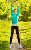 stock photo of leggins  - Young pretty woman exercising stretches on a nature background - JPG
