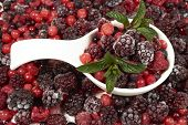stock photo of berries  - White porcelain bowl with frozen berries and mint leaves stands in the midst of other berry fruits - JPG