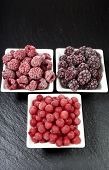 stock photo of fruit platter  - Three small porcelain dishes with frozen raspberries currants and blackberries on a slate platter - JPG