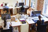 stock photo of angle  - Wide Angle View Of Busy Design Office With Workers At Desks - JPG