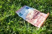 foto of depreciation  - 10 euro banknote with rain droplets lying on the grass - JPG