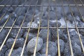 foto of charcoal  - Some charcoal briquettes unlit beneath a metal grating ready for some summer fun!